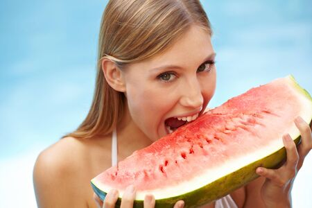 Happy attractive woman eating a watermelon in swimming pool photo