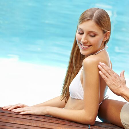 Young attractive woman in swimming pool gets her back lubed with sunscreen Stock Photo - 13560435