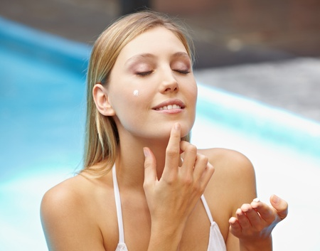 Attractive young woman in pool putting sunscreen on her face Stock Photo - 13559448