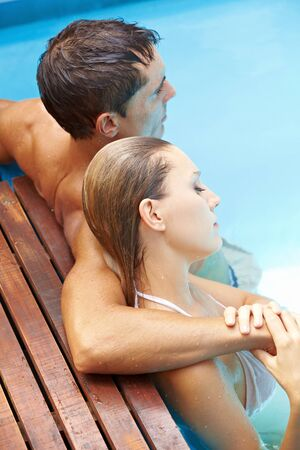 Attractive young couple relaxing together in swimming pool with blue water photo