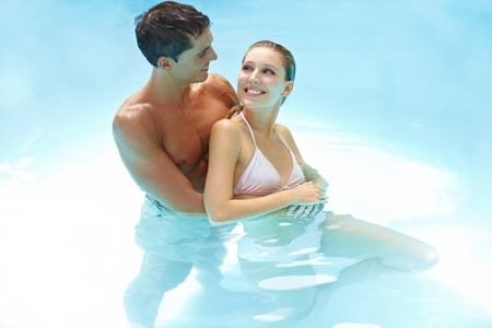 Happy smiling couple bathing together in swimming pool photo