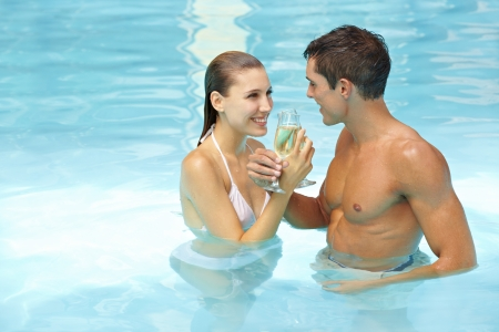 Happy couple celebrating with sparkling wine in swimming pool photo