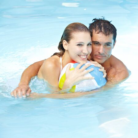 Happy attractive couple with beach ball in swimming pool photo