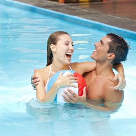 mujer ba�andose: Atractiva pareja feliz divirti�ndose en la piscina con pelota de playa Foto de archivo