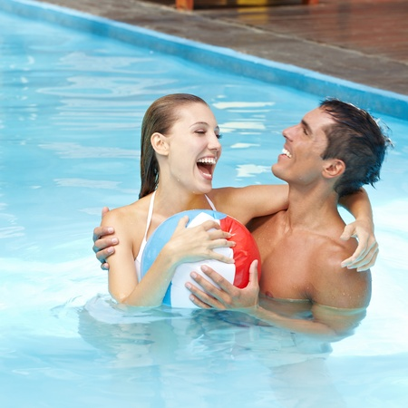 bathing man: Happy attractive couple having fun in pool with beach ball