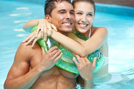 Smiling happy couple in pool with floating ring photo