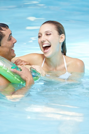 Laughing woman with happy man in floating ring in swimming pool photo
