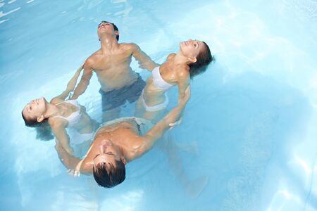 hydrotherapy: Relaxed group doing water yoga in blue swimming pool Stock Photo