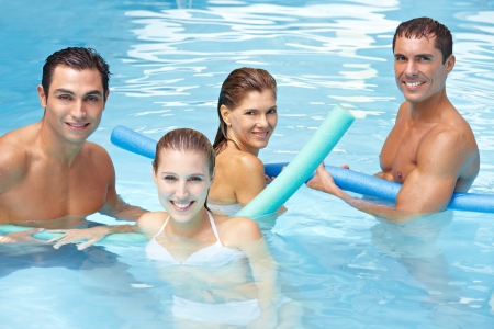 water aerobics: Happy attractive friends bathing with swim noodles in swimming pool