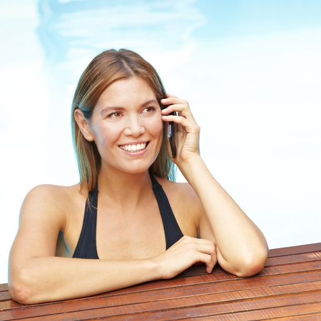 Smiling attractive woman using cell phone in swimming pool photo