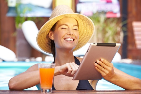 Happy smiling brunette woman with tablet computer in swimming pool photo