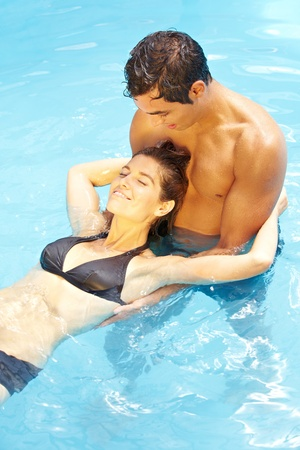 Young attractive couple relaxing together in blue swimming pool photo