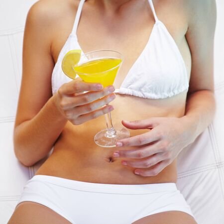Hands of a girl in bikini holding a yellow cocktail in summer photo