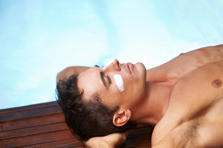 sunblock: Attractive man sunbathing with sunscreen on his face near pool Stock Photo
