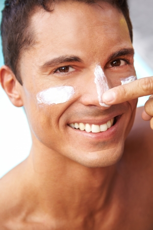 sunblock: Happy smiling man putting sunscreen and suntan lotion on his face