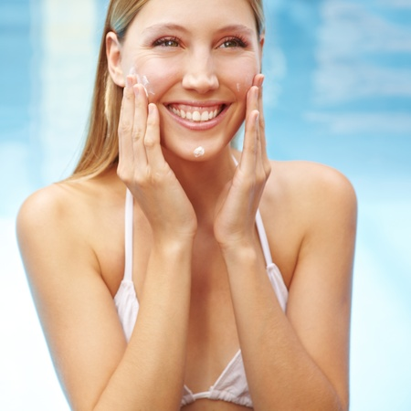 Smiling happy attractive woman putting sunscreen on her face photo