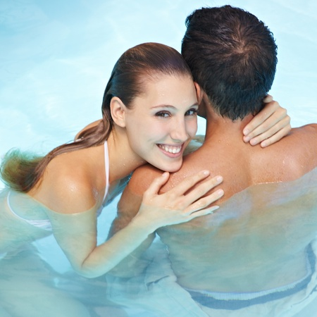 Happy smiling woman embracing attractive man in blue water photo