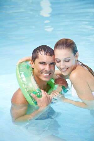 Happy smiling man learning to swim with floating ring in swimming pool photo