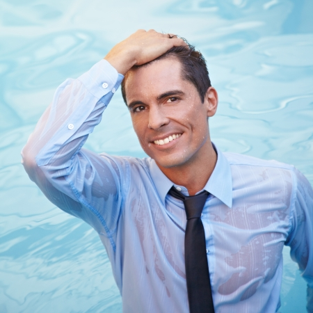 umida: Sorridente uomo d'affari con i vestiti bagnati in acqua blu Archivio Fotografico