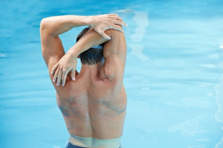 Young man doing back exercises in blue water in swimming pool photo