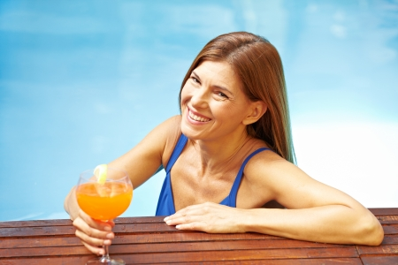 Elderly smiling woman with cocktail in a swimming pool photo