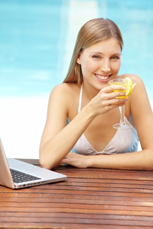 Attractive smiling woman with cocktail and laptop in swimming pool photo