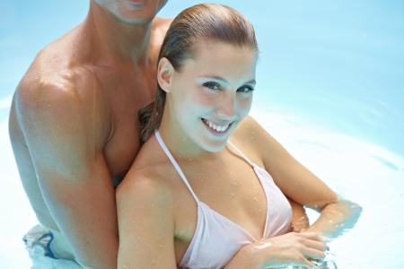 Young attractive happy couple bathing in swimming pool photo