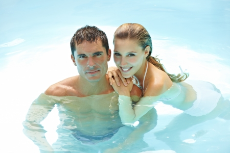 Happy attractive couple taking a bath in a swimming pool Stock Photo - 13635507