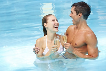 pool party: Laughing attractive happy couple with champagne wine in swimming pool
