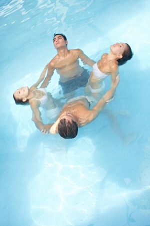 Group in a circle doing water yoga in swimming pool photo