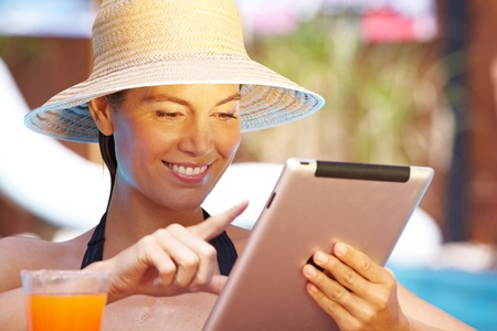 Attractive smiling woman with straw hat using tablet computer in pool photo