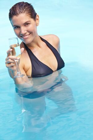 Happy woman drinking glass of sparkling wine in swimming pool photo