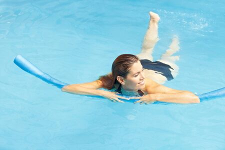 Attractive woman learning swimming with swim noodle in pool