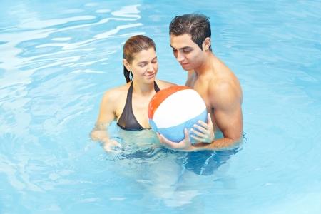 bola de billar: Atractiva pareja jugando con una pelota de playa en el agua de la piscina