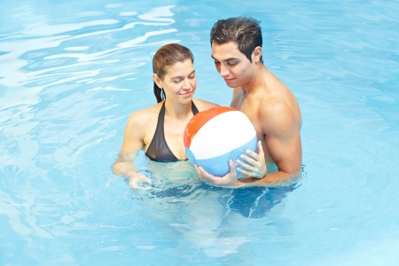Attractive couple playing with beach ball in swimming pool water photo