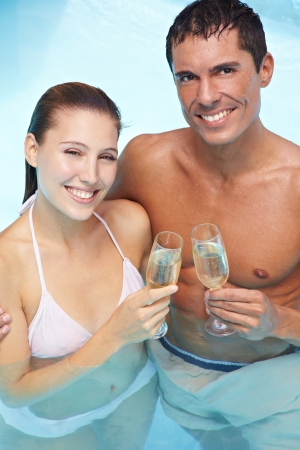 Happy smiling couple in swimming pool drinking sparkling wine photo