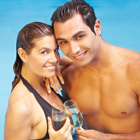 Smiling couple drinking champagne together in swimming pool photo