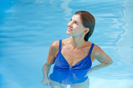Elderly attractive woman standing in swimming pool with blue water photo