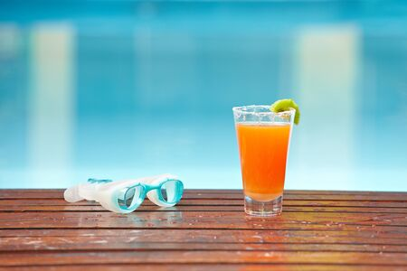 Cocktail in glas and goggles near a blue swimming pool photo