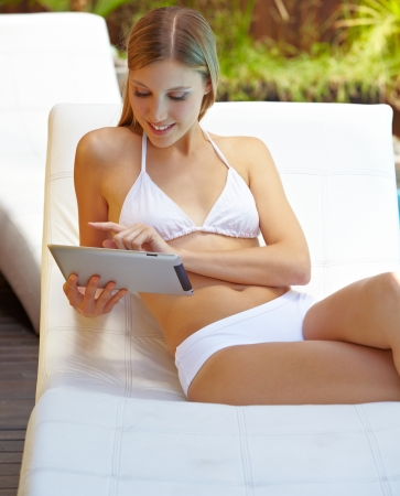 Attractive woman using tablet computer outdoors at the swimming pool photo