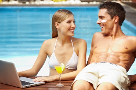 Young attractive couple with laptop at swimming pool photo