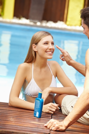 Happy young couple in holidays near pool applying sunscreen photo
