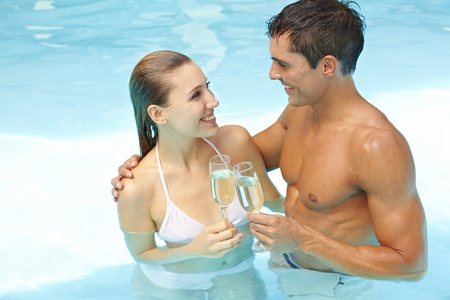Young attractive couple with champagne in swimming pool photo