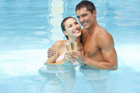 Happy attractive couple celebrating with champagne in swimming pool photo