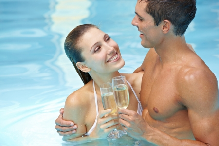 pool party: Happy attractive couple drinking sparkling wine in swimming pool Stock Photo
