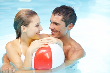 Happy smiling couple in swimming pool with beach ball Stock Photo - 13664489