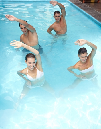 water aerobics: Happy group doing aqua fitness in swimming pool Stock Photo