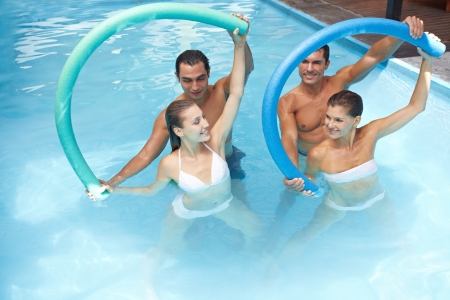 Group in swimming pool doing water aerobics with swim noodles photo