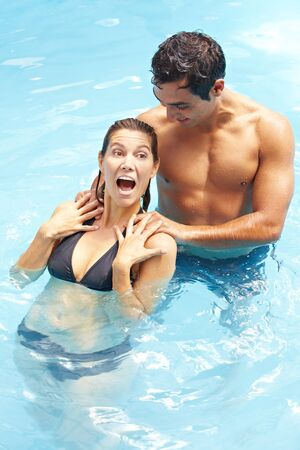 Young man massaging attractive woman in swimming pool 写真素材