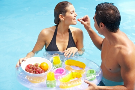Attractive couple having romantic breakfast in swimming pool